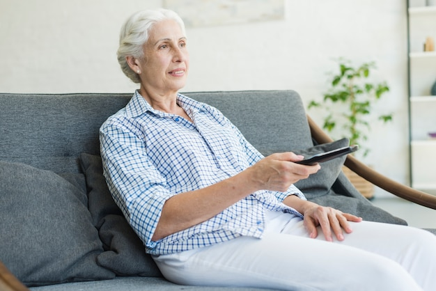 An elderly woman watching television using remote