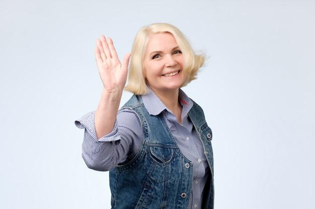 高齢者の女性が手を振って挨拶