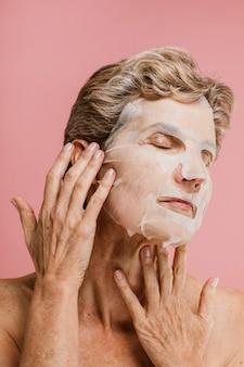 顔のマスクを身に着けている年配の女性