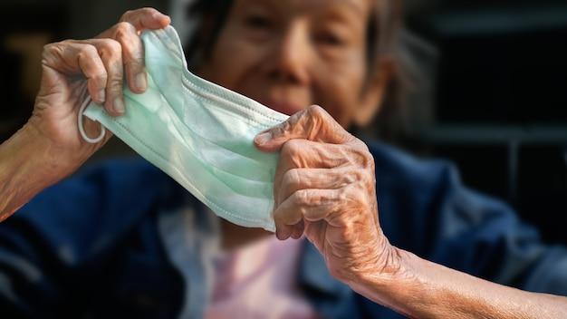 コロナウイルスcovid-19から保護するためにマスクを身に着けている年配の女性
