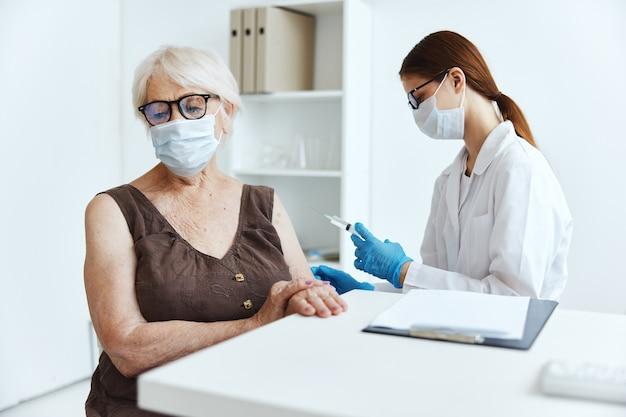 Пожилая женщина в медицинской маске в больнице для вакцинации covid паспорт