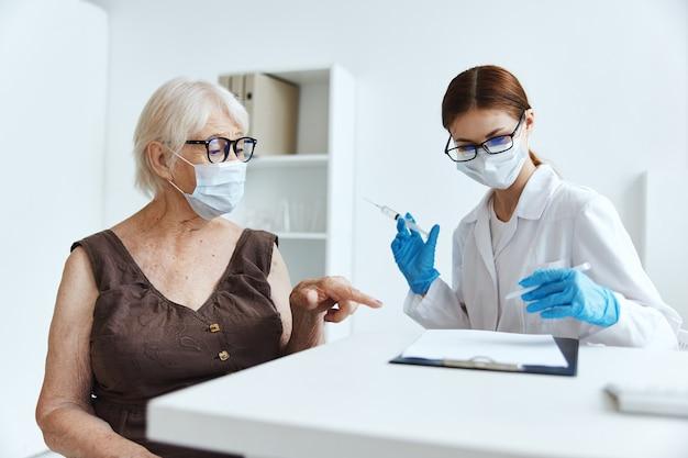 Пожилая женщина в медицинской маске в больнице для защиты иммунитета от прививок