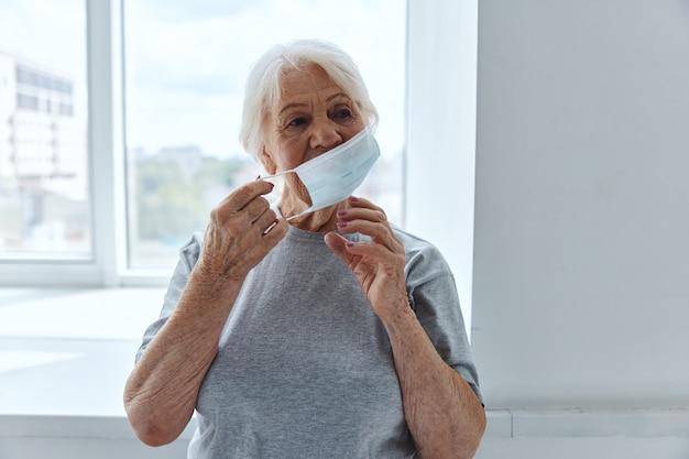 医療用マスク呼吸器疾患を身に着けている年配の女性
