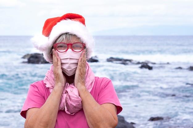 サンタの帽子をかぶってビーチに立っているcovid19のために保護マスクを身に着けている年配の女性