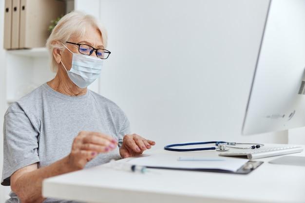 안경 의료 마스크를 착용하는 노인 여성 의사 약속입니다. 고품질 사진