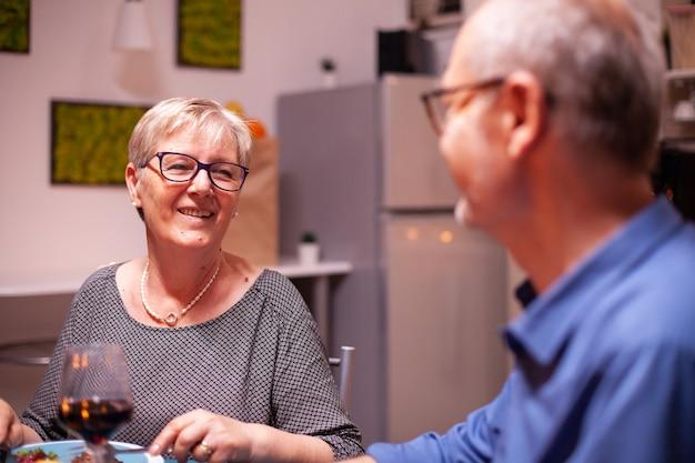 남편과 축제 저녁 식사를 하면서 안경을 쓴 할머니. 행복한 노인 부부는 아늑한 주방에서 함께 식사를 하고 기념일을 축하하며 식사를 즐기고 있습니다.