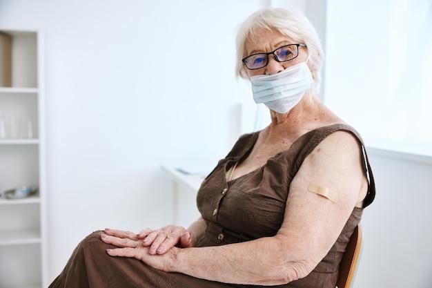 그녀의 손 covid 여권 병원에 석고와 안경을 쓰고 할머니