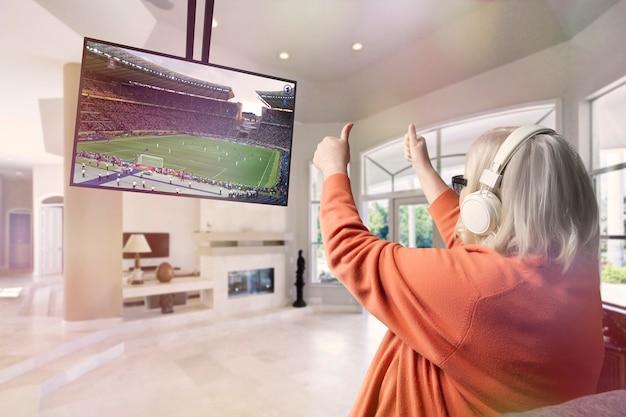 Elderly woman wearing headphones watching football on big screen