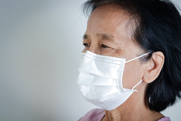 Elderly woman wearing masks, covering their mouths and noses, preventing coronavirus or covid-19.