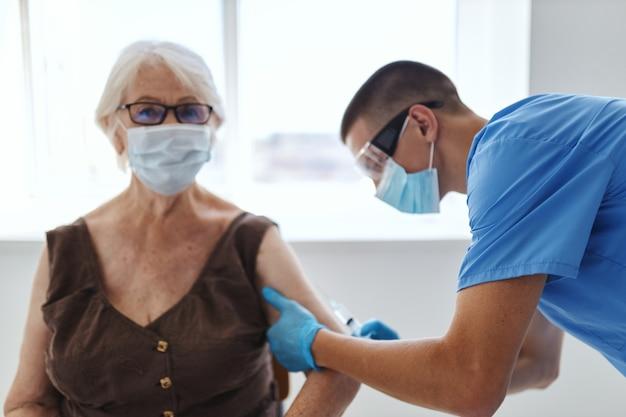 의사 주사 병원 백신 covid 여권 옆에 의료 마스크를 쓴 할머니