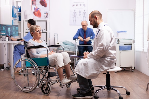 Elderly woman in wheelchair at doctor appointment in recovery clinic