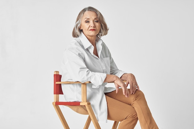 An elderly woman in a white shirt sits on a chair posing