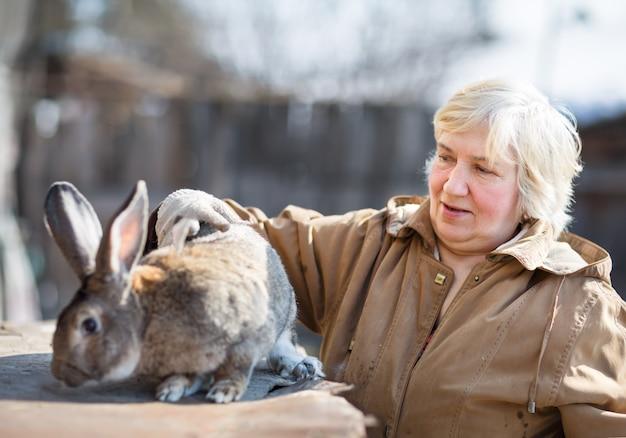 Пожилая женщина с большой кроличьей фермой