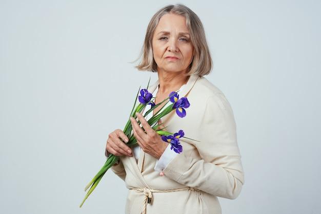 花の花束を持つ年配の女性の贈り物の思いやりのある誕生日。高品質の写真