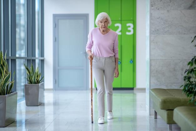Пожилая женщина с тростью гуляет по коридору