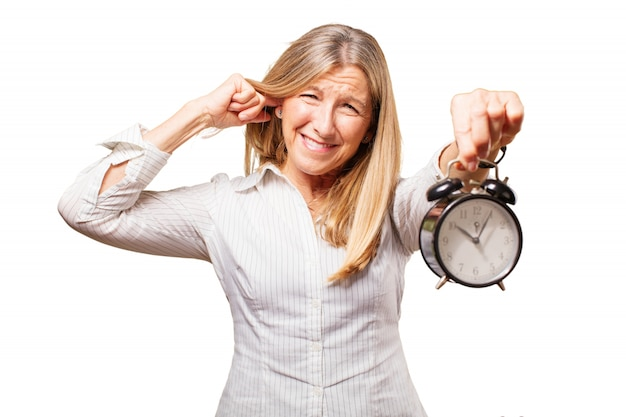 Elderly woman with an alarm clock doing like it hurts her ear