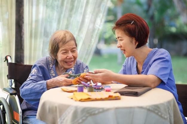 Пожилая женщина с опекуном в процессе трудотерапии рукоделия от болезни альцгеймера или деменции