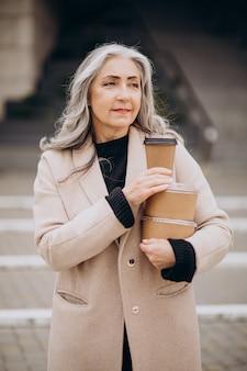 Пожилая женщина с едой забирает коробки