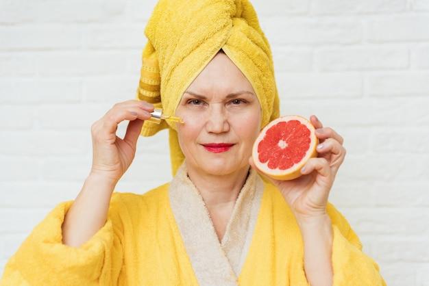 Пожилая женщина с грейпфрутом и пипеткой для масла. концепция ухода за кожей и морщинами