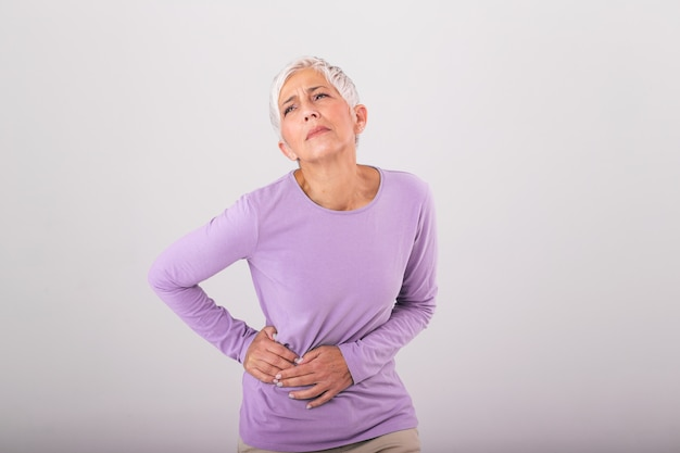 Elderly woman with gray hair touching her aching hip. upset mature old woman touching back feel hurt osteoarthritis kidney spine ache sore muscles