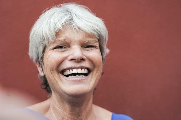 携帯電話を使って自分撮りをしている白髪の老婆-高齢者はテクノロジーを楽しむ
