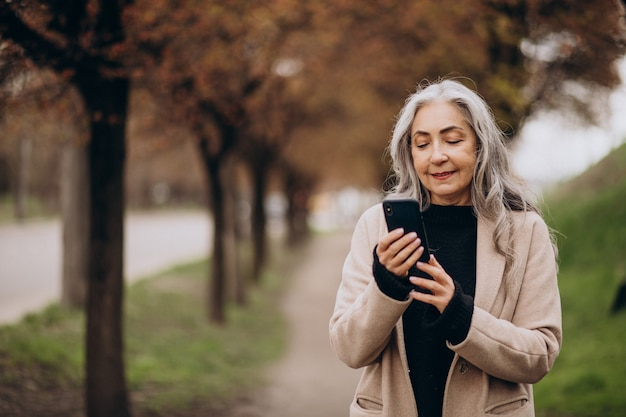 Пожилая женщина с серыми волосами разговаривает по телефону в парке