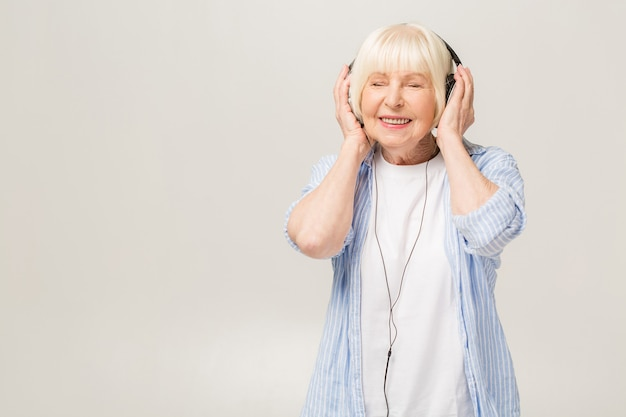 Elderly woman with headphones listening to music on a phone isolated on white background