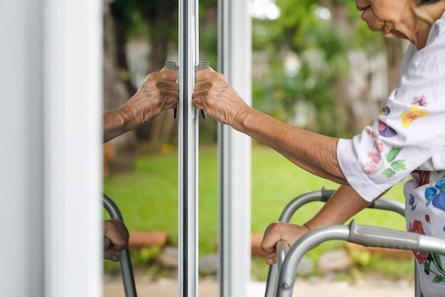 Elderly woman with key opening front door.