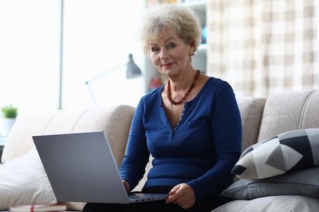 Пожилая женщина с ноутбуком сидит на диване