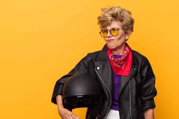 泡のジャケットとモーターサイクリストのヘルメットを持つ年配の女性