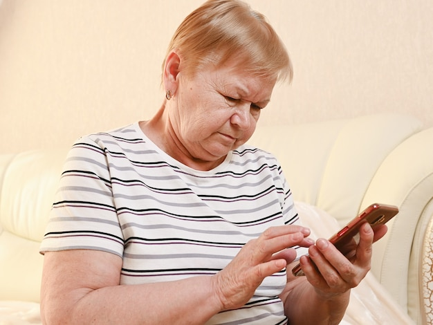 Elderly woman with mobile phone at home.