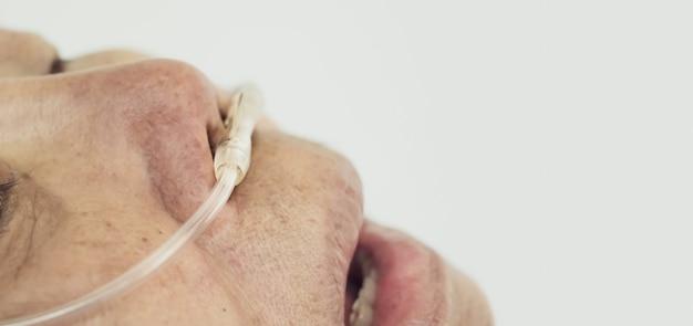 집에서 그녀의 호흡을 돕기 위해 코 호흡 튜브를 가진 노인 여성