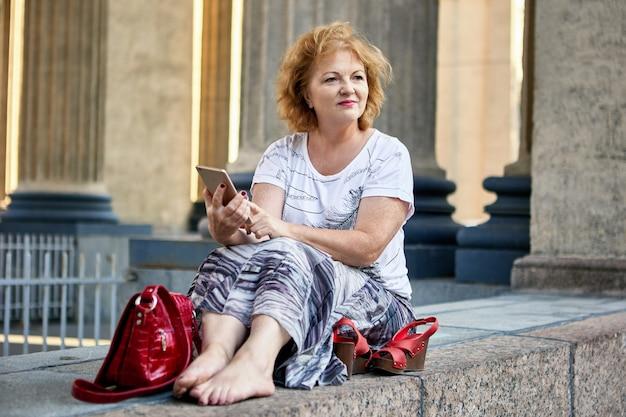 Пожилая женщина с телефоном сидит на улице на каменной лестнице