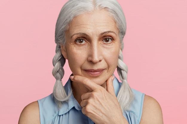Пожилая женщина с косичками позирует