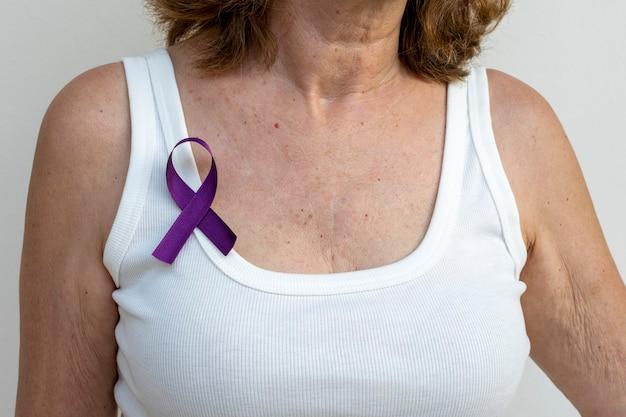 Пожилая женщина с лентой с фиолетовым бантом на футболке.