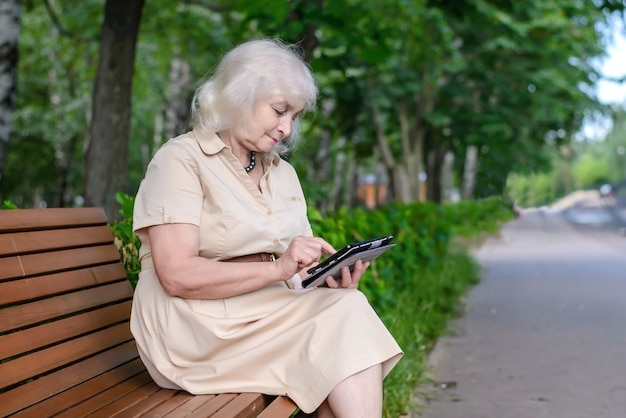 An elderly woman with tablet computer in the park