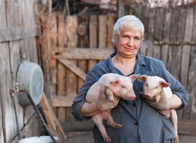 Пожилая женщина держит в руках двух поросят. животноводство