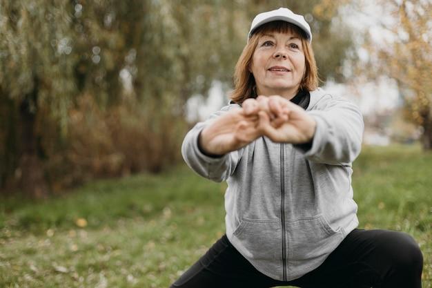 Пожилая женщина работает на открытом воздухе с копией пространства