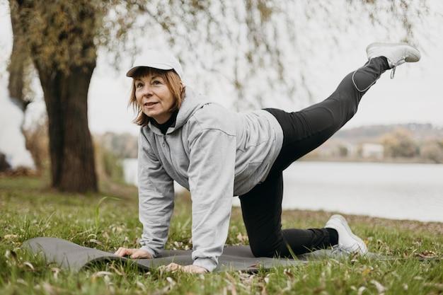 Donna anziana che lavora fuori all'aperto