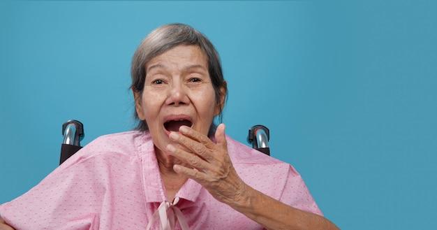 Elderly woman yawning on wheelchair