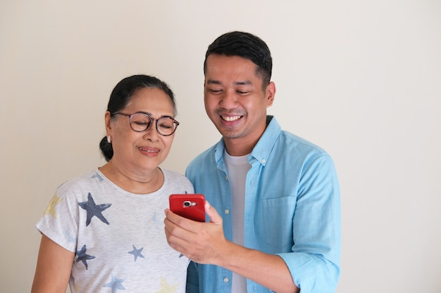 Elderly woman and young man smiling together while looking to mobile phone
