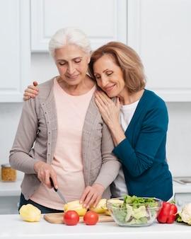 Elderly women cutting vegetables