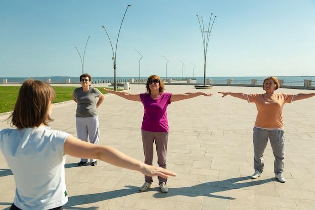공공 공원에서 트레이너와 함께 스포츠 훈련을 하는 노인 여성, 질병 후 레크리에이션 피트니스. 스포츠 훈련과 함께 건강한 생활 방식을 가진 연금 수령자 여성.