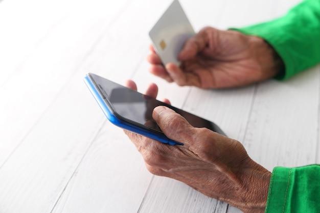 年配の女性がクレジットカードを持ってスマートフォンをオンラインショッピング