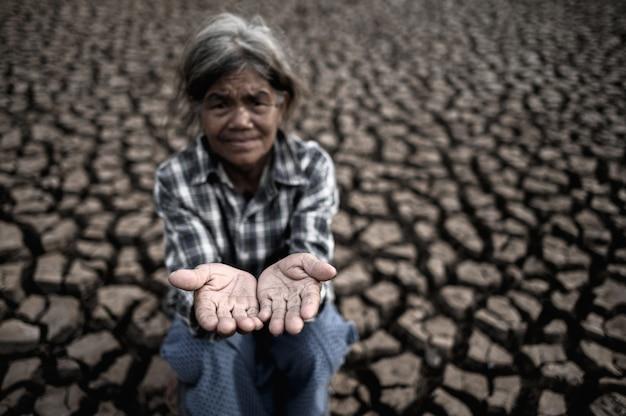 노인 여성은 건조한 날씨, 지구 온난화, 선택된 초점에서 빗물을 얻기 위해 손을 잡습니다.