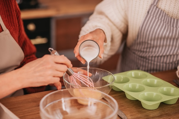 ボウルに牛乳を注ぐ年配の女性