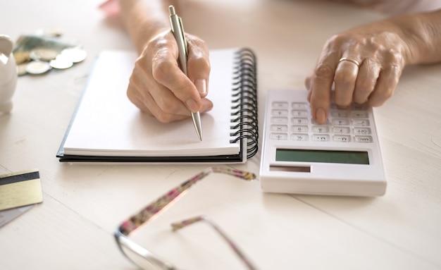 Пожилые женские руки считают расходы, планируют бюджет концепции пенсии, сбережений, старости.