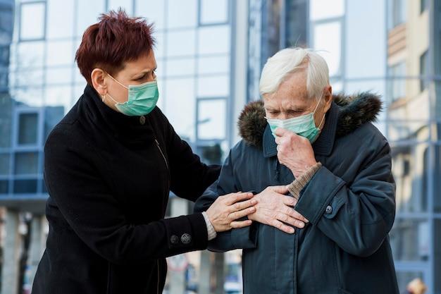 市内にいる間に気分が悪くなる医療用マスクを持つ高齢者の女性