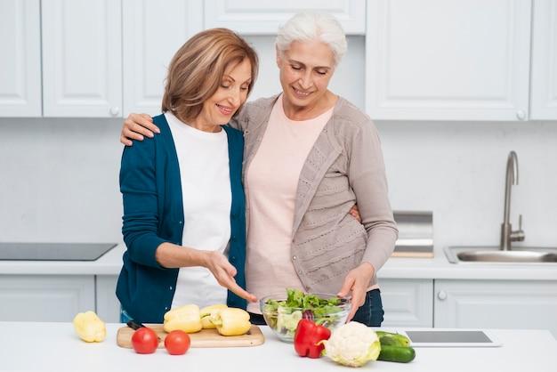 테이블에 채소와 노인 여성