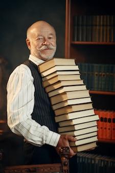 高齢作家がホームオフィスで本のスタックを保持しています。